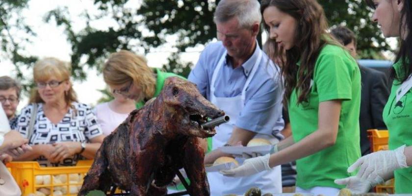 Zdjęcie przedstawia upieczonego dzika na stole oraz gotujących ludzi