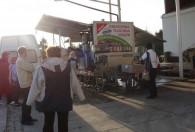 grupa ludzi stojąca obok mobilnej tłoczni soków